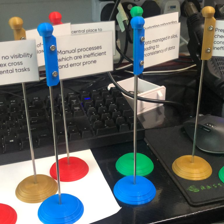 Card stands with round FDM 3D printed bases and card attachments in red, blue, green and gold materials