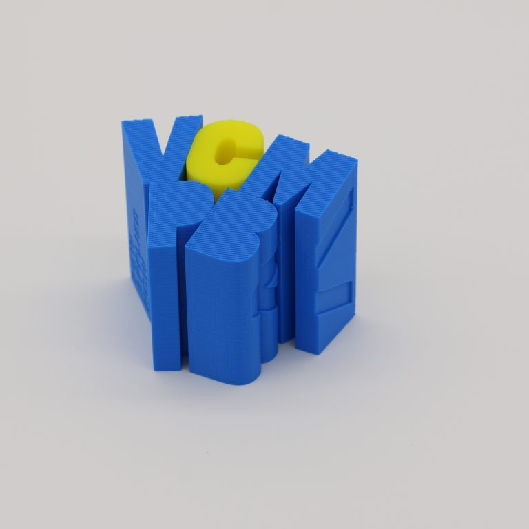 FDM 3D printed text blocks assembled into a group of characters in blue and yellow materials